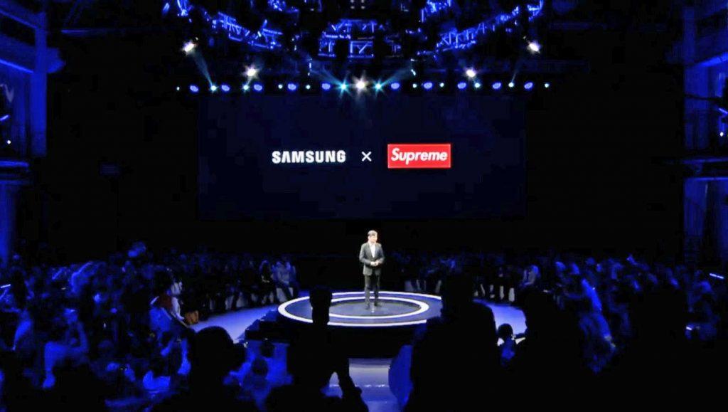 persona su palco per la presentazione del nuovo galaxy a8s con schermo dietro raffigurante i loghi di samsung e supreme