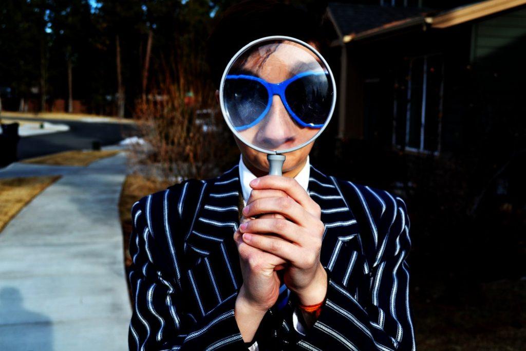 uomo che tiene in mano una lente d'ingrandimento di fronte al viso