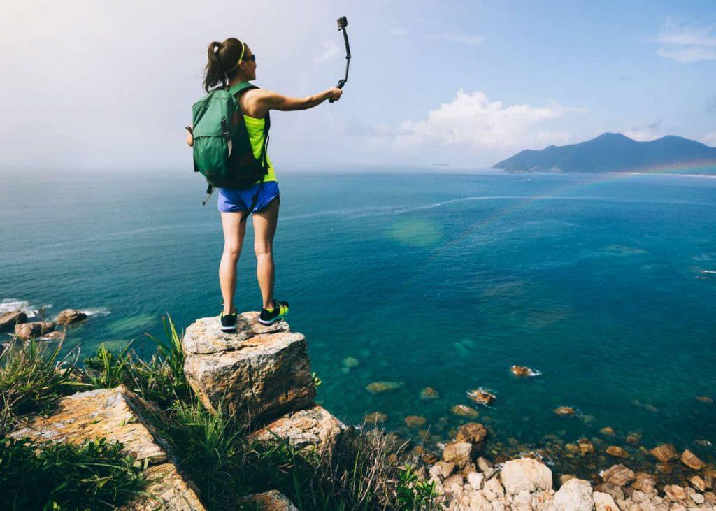 Un ragazzo scatta una foto con gopro ad un panorama marittimo. Esempio di User Generated Content