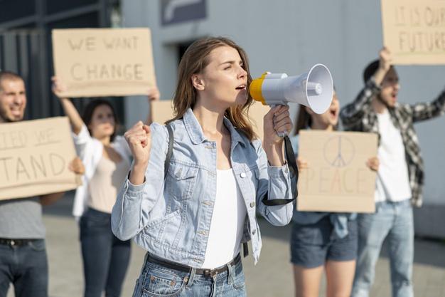 Delle persone protestano per sostenere una loro ideologia. In primo piano, una ragazza parla con il megafono. Fonte: Marketing Ignorante