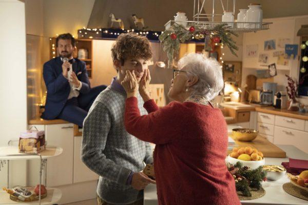 Spot di Natale Bauli. Una nonna stringe le guance del nipote per dimostrargli affetto. Sullo sfondo un cantante è seduto sulla credenza della cucina per cantare la nuova canzone della pubblicità. Fonte: Marketing Ignorante