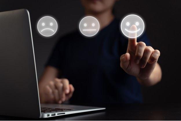 Una donna seduta al pc, valuta la sua customer experience cliccando sul simbolo di una faccina felice. Fonte: Marketing Ignorante