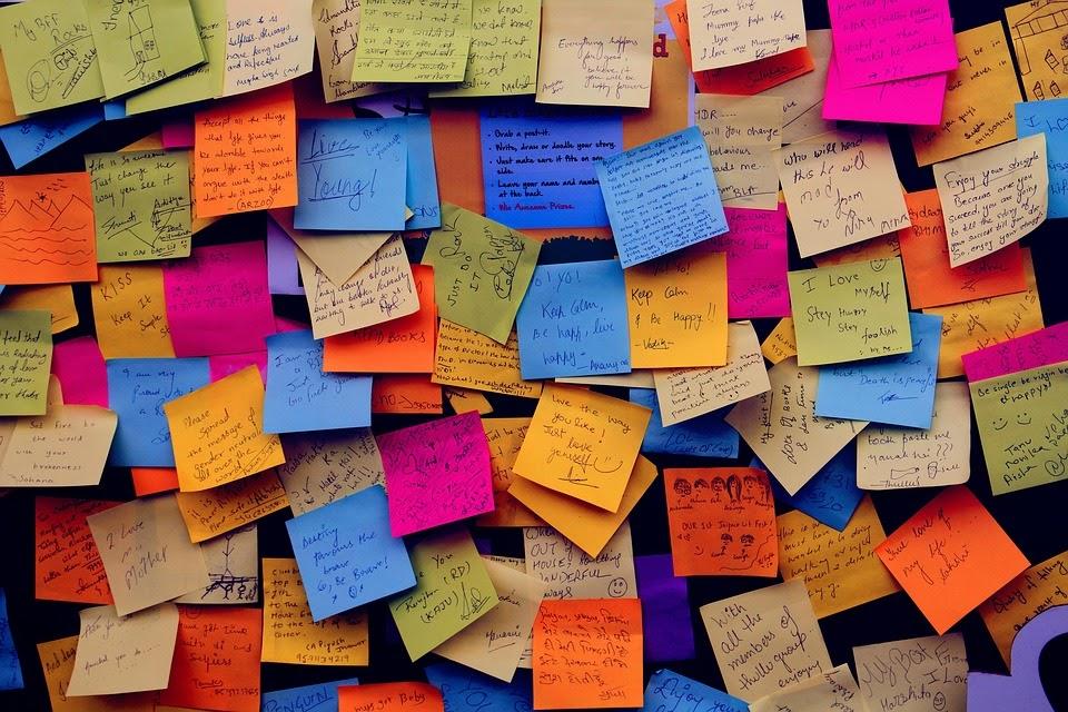 La storia dell'invenzione post-it è mostrata nell'immagine grazie a tanti segnapagine colorati con molte scritte attaccati al muro.
