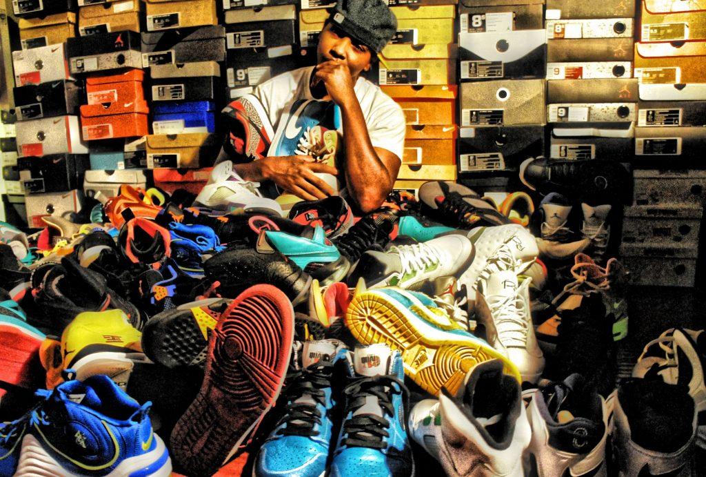 Un ragazzo abile nel reselling seduto tra una montagna di scarpe da collezione e poggiato su un muro fatto di scatole di sneakers. Fonte: Marketing Ignorante