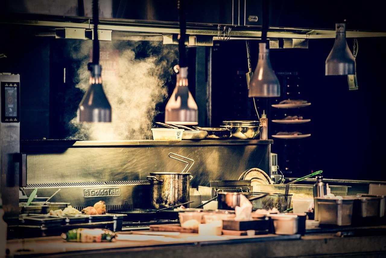 Dark kitchen e ghost restaurant spopolano in Italia. Cucina con sfondo nero, pentole e griglie in evidenza. Sullo sfondo del fumo esce dalla pentola. Fonte: Marketing Ignorante