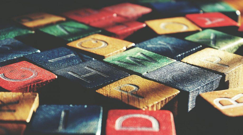 Brand naming: lettere stampate su tasselli di legno colorati, disposti uno accanto all'altro.