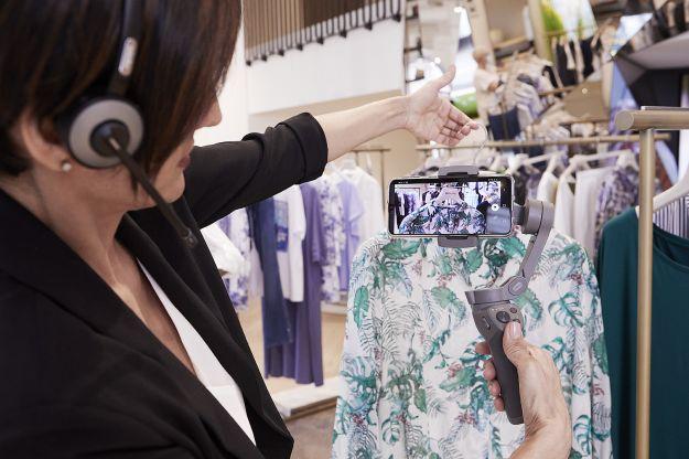 Addetta alle vendite Elena Mirò mostra, attraverso uno smartphone un capo d'abbigliamento in diretta alla cliente, guidandola nell'acquisto. Fonte: FashionMagazine.it