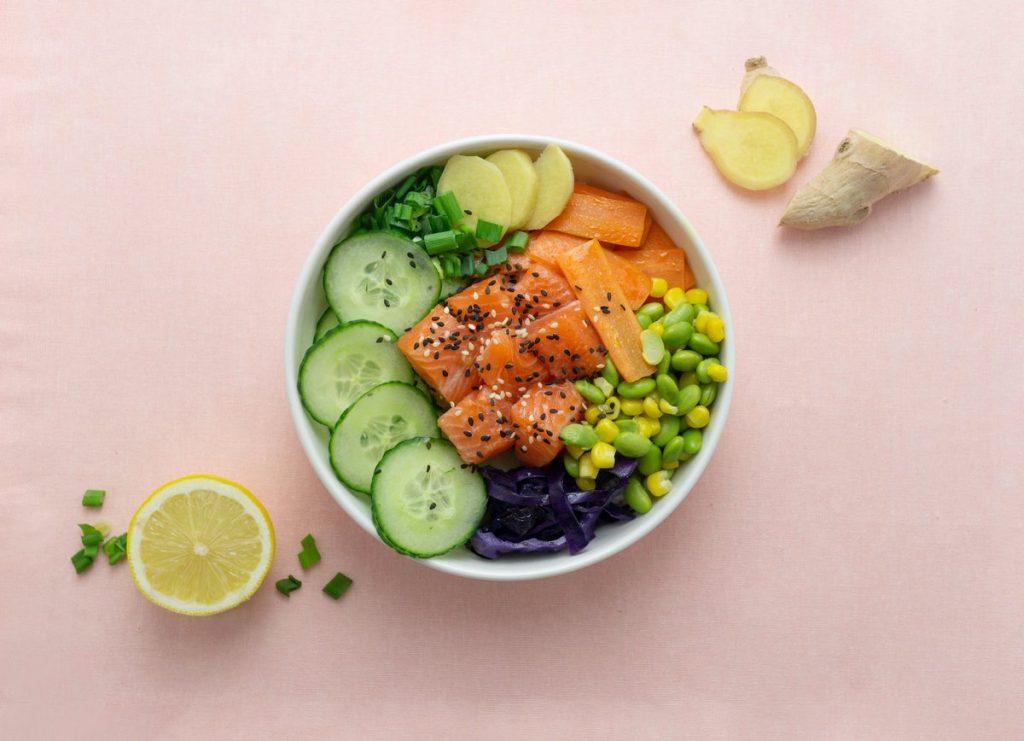 Poke Bowl di salmone, cavolo nero, cetriolo, edamame, mais, patate, carote, erba cipollina e sesamo