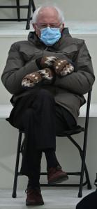 Bernie Sanders, senatore del Vermont, fotografato seduto con le gambe accavallate  e le braccia una sull'altra, alla cerimonia dell'Inauguration Day. Indossa guanti, mascherina ed ha un'espressione annoiata.
