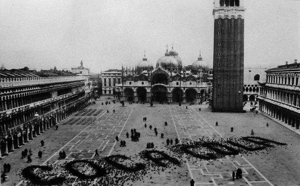 Piccioni che, beccando il mangime in piazza San Marc a Venezia, formano la scritta Coca-Cola