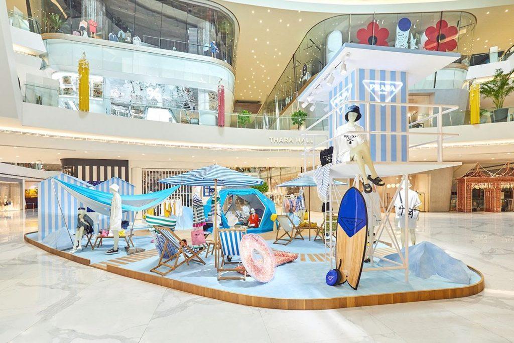 #PradaOutdoor con i suoi pop-up store e installazioni in-store. L'immagina mostra il summer marketing dell'azienda attraverso una delle installazioni che richiama un contesto esitivo con accessori tipici come le sdraio, gli ombrelloni, le tende etc...