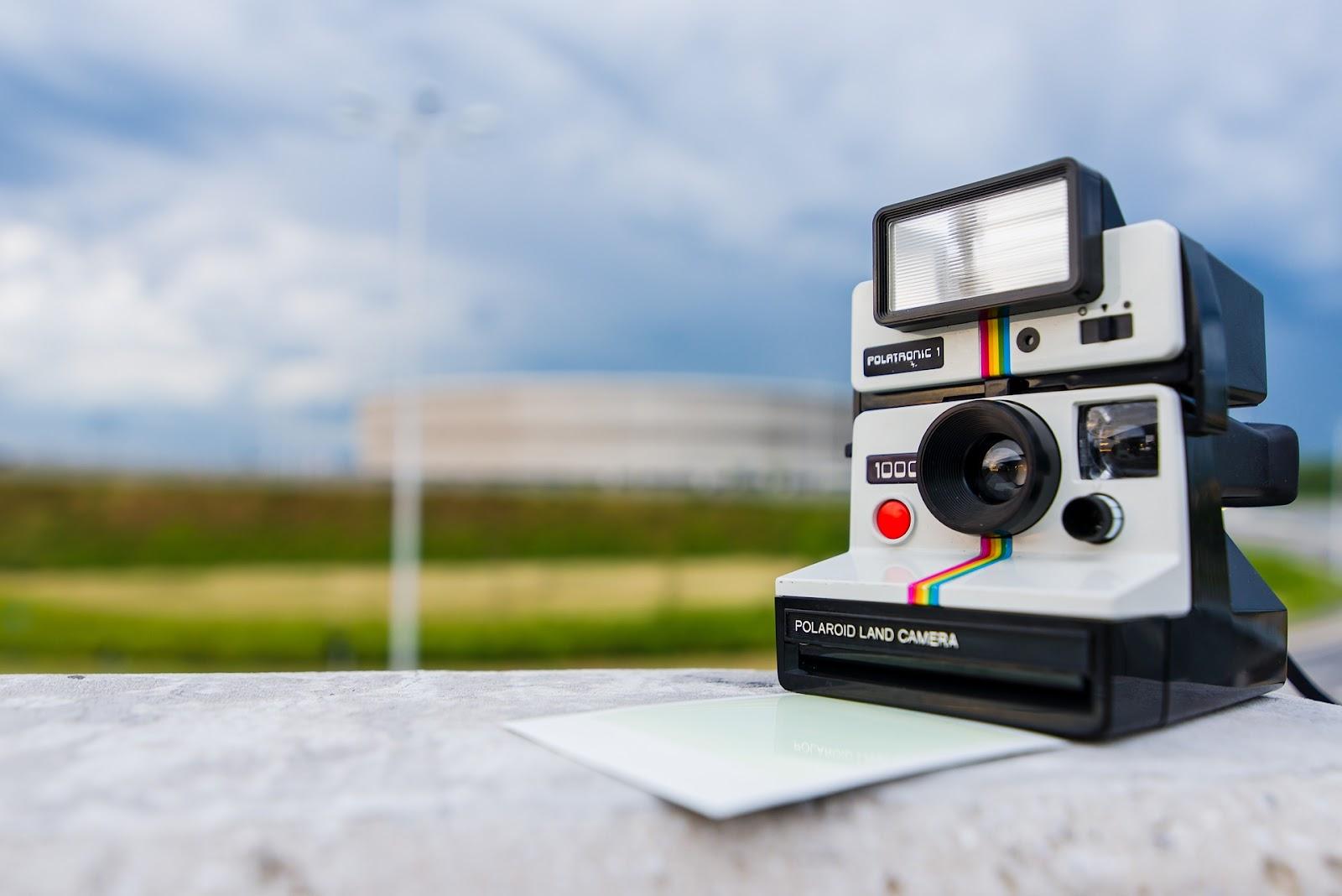 Fotocamera di Polaroid appoggiata su un muretto, con natura nello sfondo per introdurre la storia di Polaroid